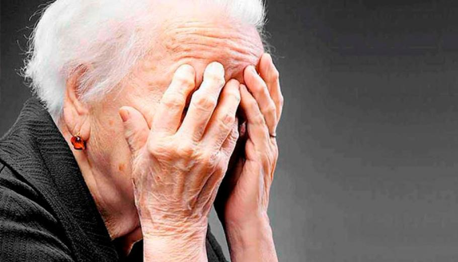 An older woman covering her face with her hands